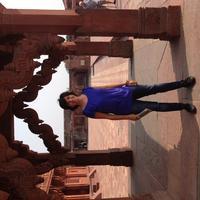 Asli Niyazioglu standing outside under a carved stone archway