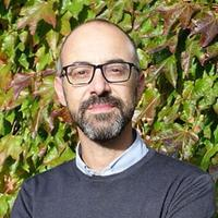 Photo of Giuseppe Marcocci smiling to camera with foliage behind him.