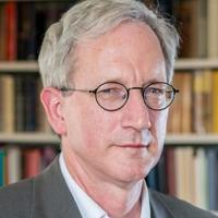 Headshot of Howard Hotson looking to camera with bookshelf in background.
