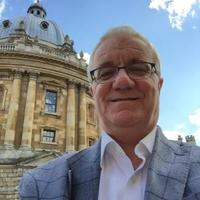 Photo of Ian Archer smiling standing in front of the Radcliffe Camera