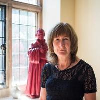 Lyndal Roper standing in front of a window which has a statue on the windowsill - possibly Martin Luther.