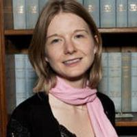 Headshot of Sarah Mortimer smiling to camera, standing in front of a bookcase.